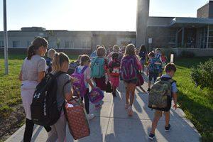 children and teachers walk to school entrance