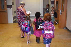 3 girls wearing new backpacks following teacher in hallway