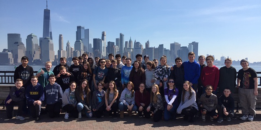 group of students with NYC skyline behind them