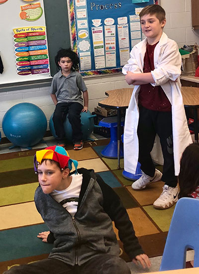 3 students dressed in costumes doing a role play