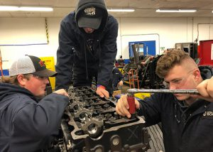 3 male students work on diesel engine