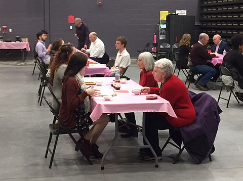 group of students interviewing group of seniors, all seated at tables