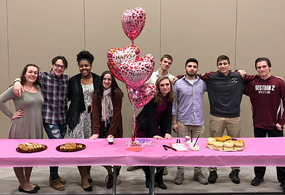 group of students standing behind table with heart balloons