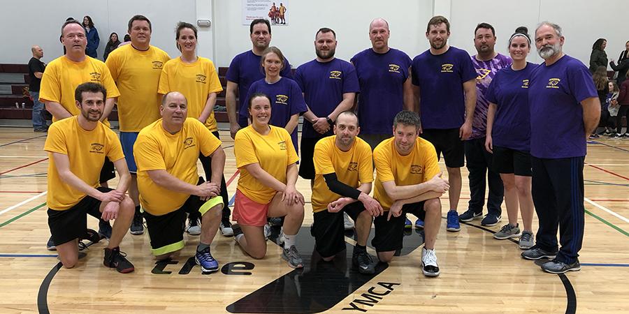 staff members pose on basketball court