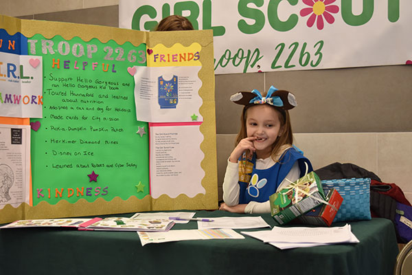 Girl Scout sits at booth