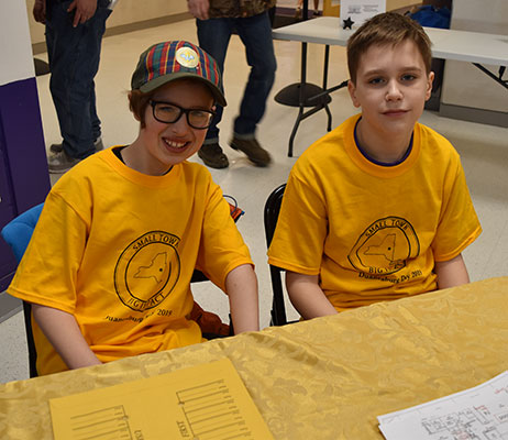 2 students sit at welcome table