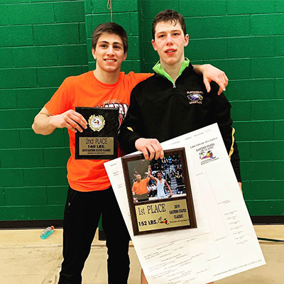 Charlie holding plaque and Zach holding plaque and poster