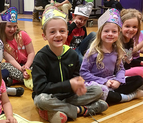 children dressed as pirates sitting on gym floor