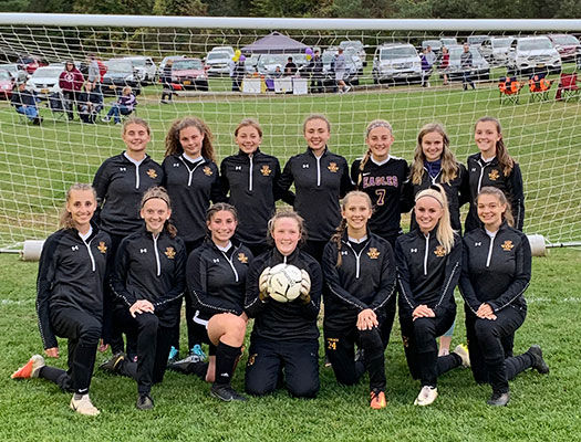 girls soccer team poses with ball on field