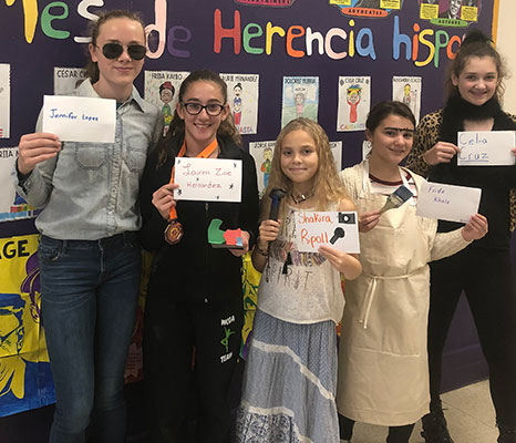 students holding cards with names of Hispanic Americans and standing in front of bulletin board