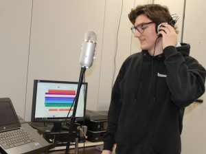 a high school student holds headphones to their ear and sings in a mock recording studio in a high school classroom