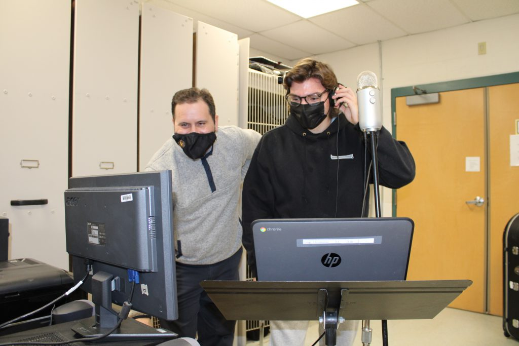 high school music teacher wearing a mask works on a computer while student wearing a mask holds headphones to his ear in a school classroom