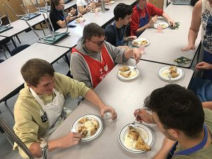 group of students sit at cafeteria tables and eat apple pie with ice cream