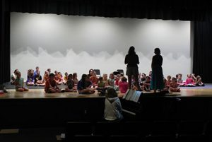 children and directors rehearse on stage
