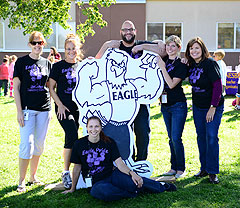 teachers pose with eagle figure on school lawn