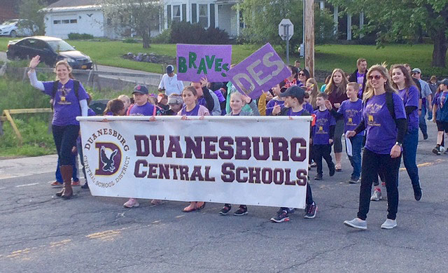 staff and students carrying parade banner