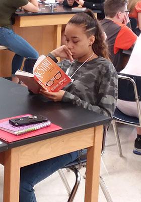"seated girl reading the book ""Restart"""