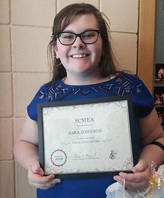 Sara Johnson holding scholarship certificate