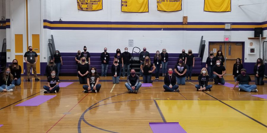 high school faculty members wearing black t-shirts and jeans in a school gymnasium