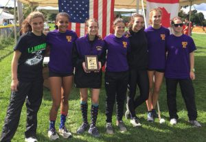 7 girls cross country team members stand holding award plaque