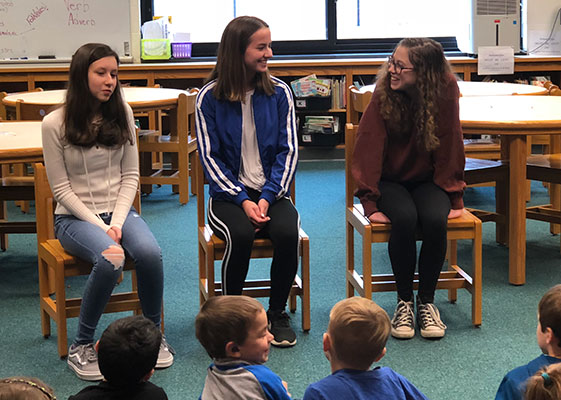 three high school students sit on chairs in front of first graders in the library