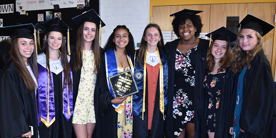 8 students in cap and gown before graduation