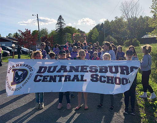 students and staff holding school banner at parade