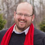portrait of a person with short hair, glasses, and a beard while wearing a red scarf
