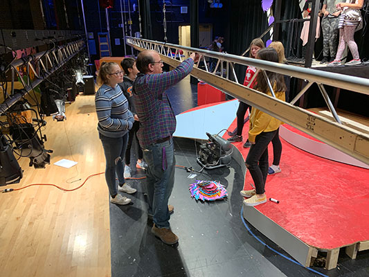 students and teacher working with rigging on stage