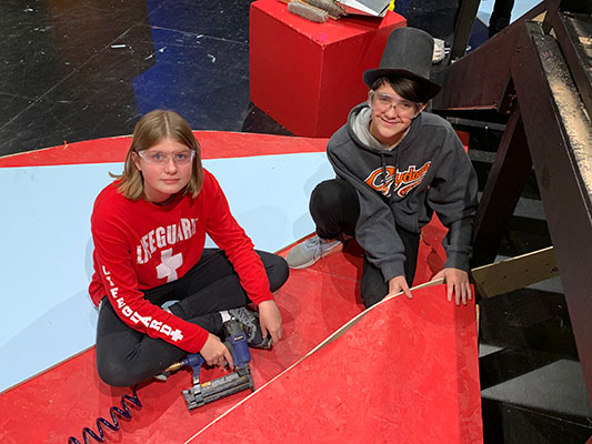 a female and a male student working with staple gun on set on stage