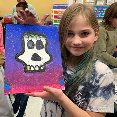 girl holding her sugar skull painting