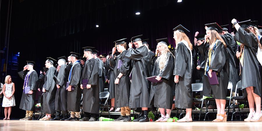 graduates turn their tassels on stage